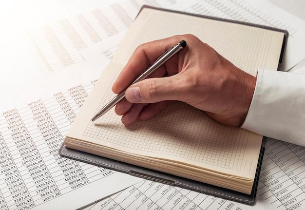 彼のビジネスをノートブックで計画している男性の手。