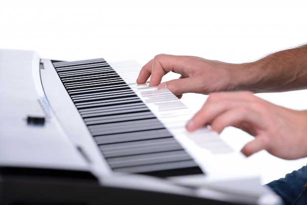 Male hands playing digital piano on white.