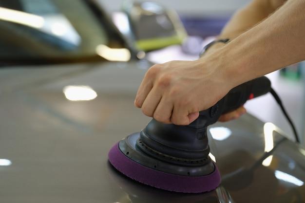 特別な機械のクローズアップで車のフードを磨く男性の手