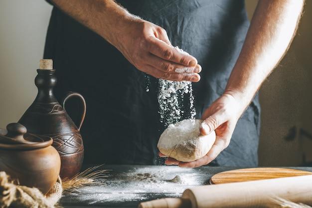 수컷 손은 요리하는 동안 진흙 냄비와 기름병 옆에 있는 반죽에 밀가루를 붓고 어두운 테이블에 롤링 핀을 붓는다