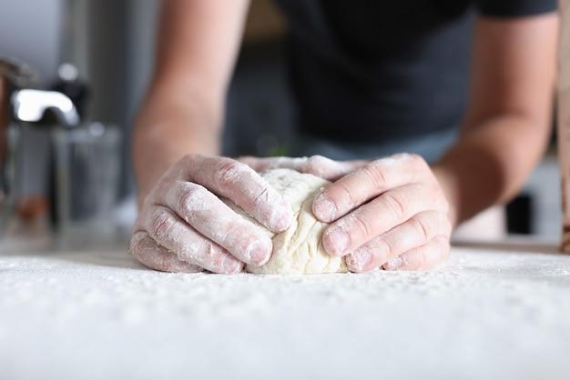 男性の手がキッチンで生地を準備します