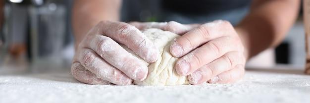 Male hands prepare dough in kitchen.