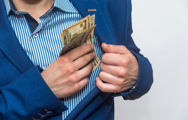 Male hands putting dollar banknotes into pocket