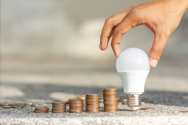 Male hands putting led bulb coin stack growing business