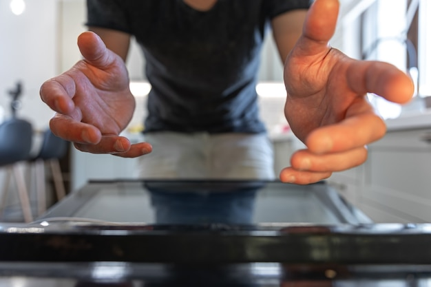 Male hands reach for the open oven to get something.