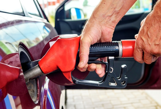 Male hands refueling a passenger car hold a red fuel pump.