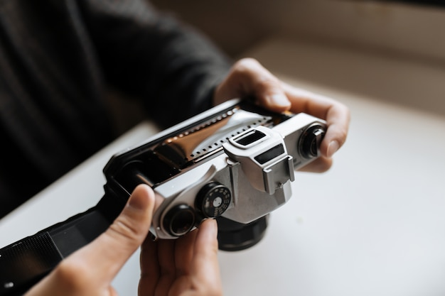 Male hands reloading film retro camera on a white table