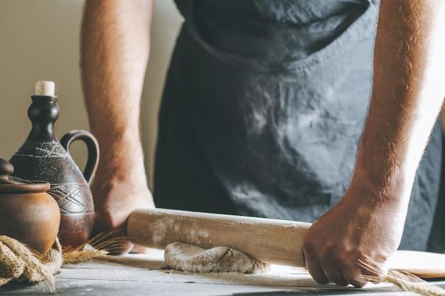 수컷 손은 요리하는 동안 진흙 냄비 옆에 있는 롤링 핀과 어두운 탁자에 있는 기름 병으로 반죽과 밀가루를 굴린다