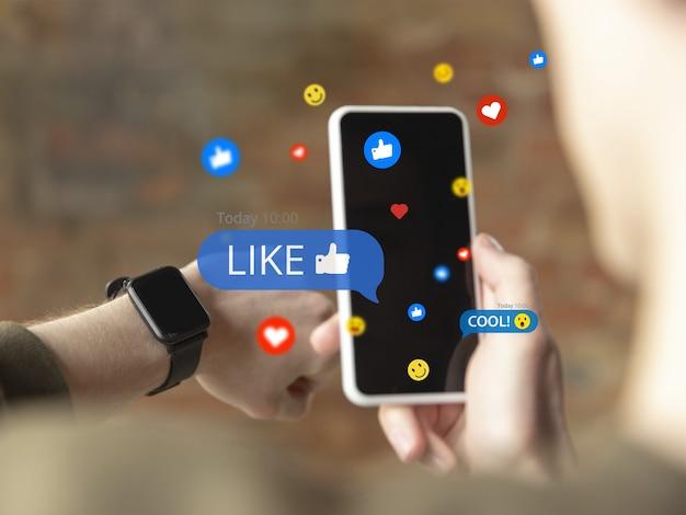 男性の手が携帯電話をスクロールし、ガジェットを使用してソーシャルメディアと共有します。コメント、いいねを取得します。最新のuiアイコン、通信、デバイス。現代のテクノロジー、ネットワーキング、ガジェットの概念。設計。