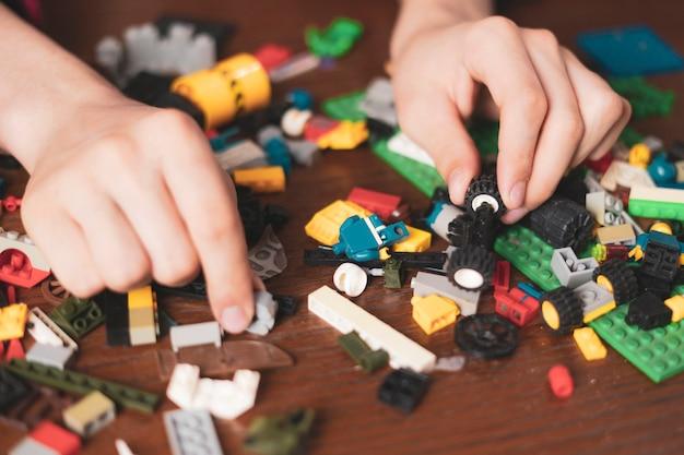 Мужские руки ищут подходящий игрушечный блок на деревянном столе b
