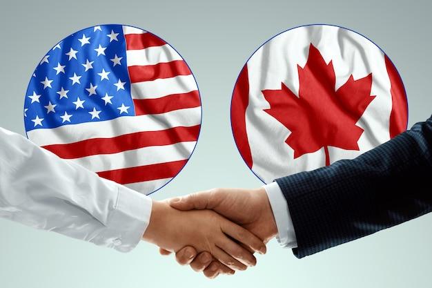 미국과 캐나다 국기의 배경에 대해 악수하는 남성 손