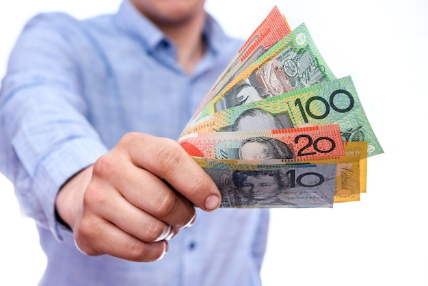 オーストラリアドル紙幣を示す男性の手がクローズアップ