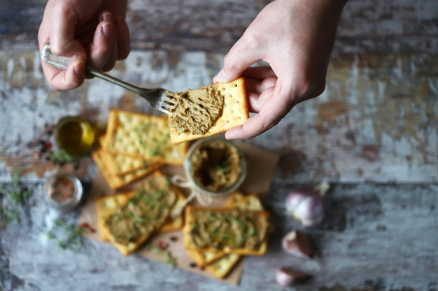 Male hands smear homemade paste on cracker. fresh homemade pate.