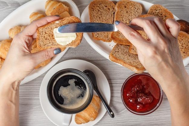 남성 손은 블랙 커피와 크루아상, 빵, 배경에 잼이 있는 유리 그릇과 함께 토스트에 버터를 뿌리고 있습니다. 평면도. 아침 식사를 위한 음식과 음료