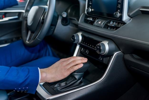 Male hands on steering wheel, car interior