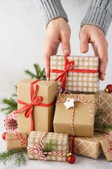 선물의 큰 스택에서 선물 상자를 복용하는 남성 손