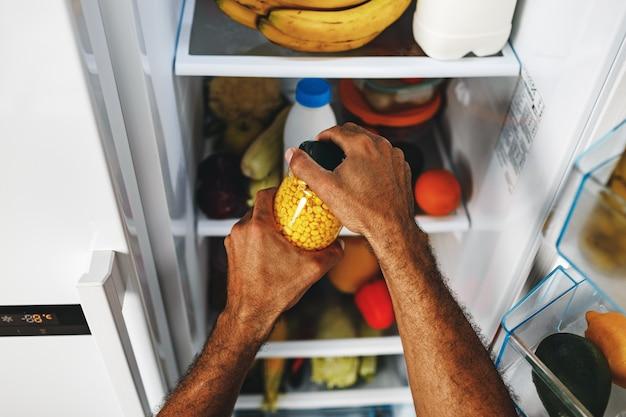 缶詰のトウモロコシの瓶を冷蔵庫から取っている男性の手がクローズアップ