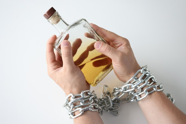 Male hands tied with chain and hold bottle of alcohol addiction and alcoholism concept