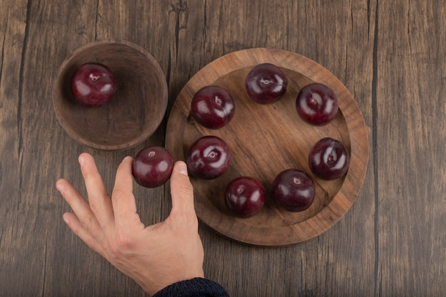 Male hands touching fresh juicy plums on wooden surface
