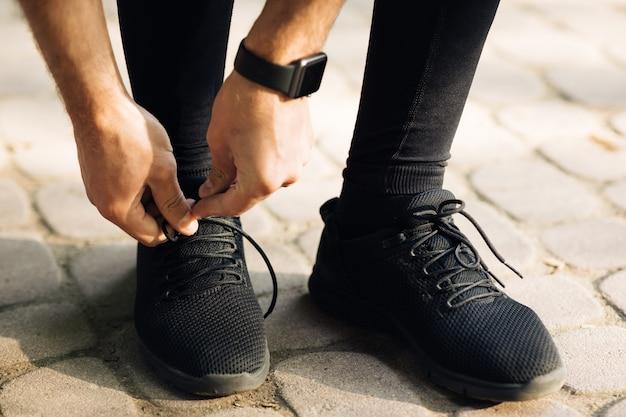Мужские руки, завязывающие шнурки на спортивных кроссовках, бегут на тренировке