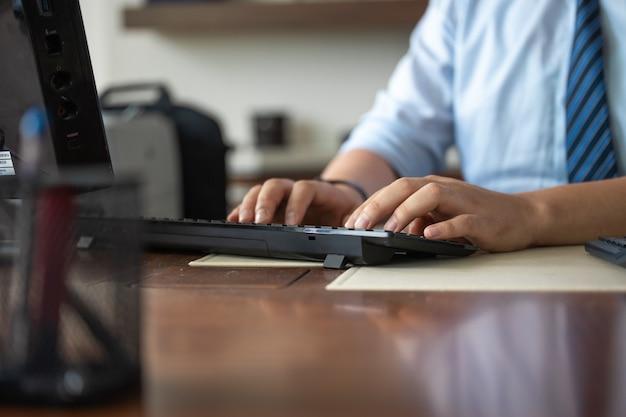 Мужские руки, набрав пальцы на клавиатуре на рабочем месте