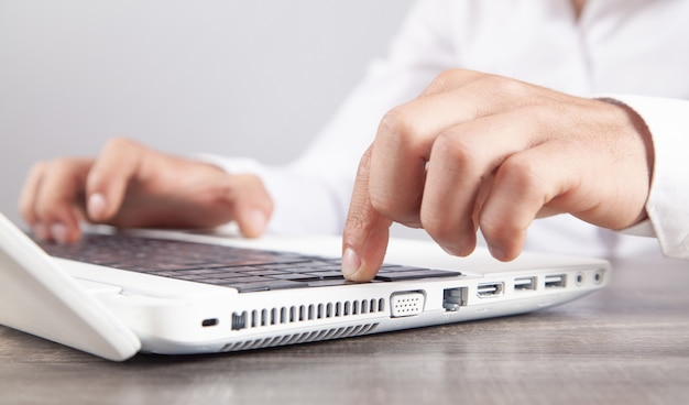 コンピューターのキーボードで入力する男性の手。