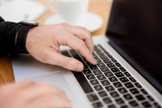 ノートパソコンのキーボードで入力する男性の手。ビューをカットします。現代のガジェット。閉じる。灰色のラップトップ。背景にぼやけた一杯のコーヒー。黒のシャツを着た男。カフェで働く男性フリーランサー。