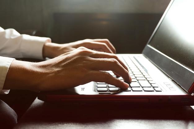 Мужской руки, набрав на клавиатуре ноутбука, фрилансер человек, работающий с цифровым компьютером, отфильтрованное изображение, кросс-процесс, вспышка солнечного света