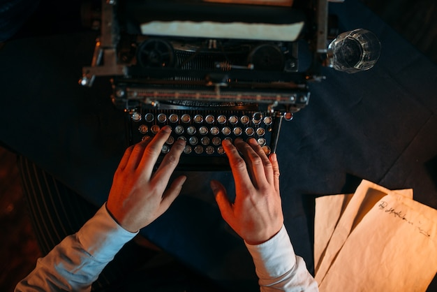 Male hands typing on retro typewriter