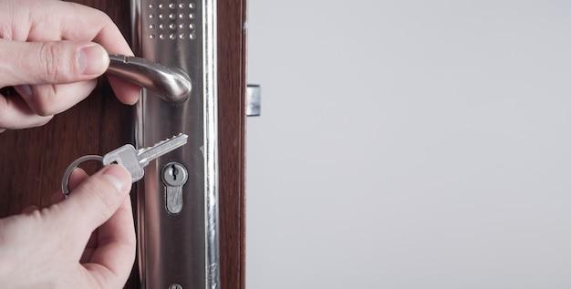 Male hands unlocking door with key.