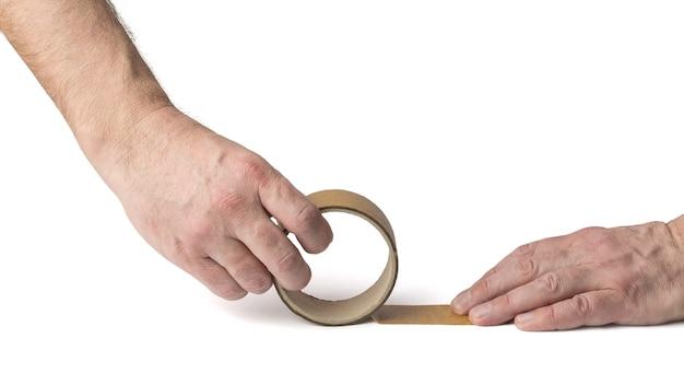 Мужские руки разматывая упаковочную ленту, изолированную на белом. универсальная упаковочная лента.