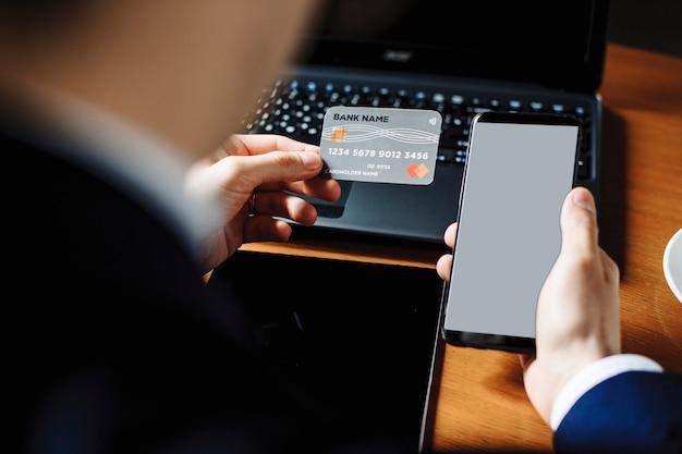 机の上にラップトップを置いて机に座っているときにクレジットカードとスマートフォンを使用して男性の手。