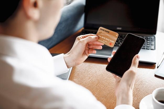 机の上に座ってクレジットカードとスマートフォンを使用する男性の手。