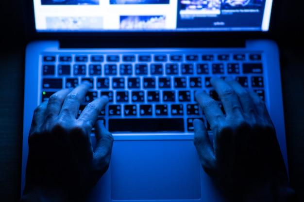 暗闇の中でラップトップを使用して男性の手