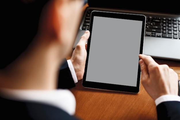 ノートパソコンを載せた机に座ってタブレットを使用する男性の手。
