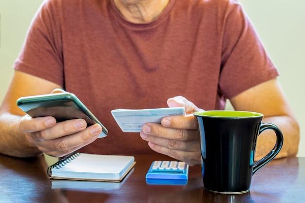 デスクで電卓アプリを使用する男性の手