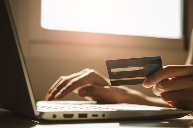 ラップトップコンピューターを使用し、自宅で仕事を中断しながらオンラインショッピングの作業デスクでクレジットカードを保持している男性の手、電子商取引、インターネットバンキング