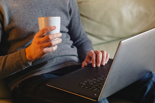 Male hands using laptop at home