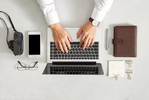白い机で黒い画面でラップトップを使用して男性の手。事務用品