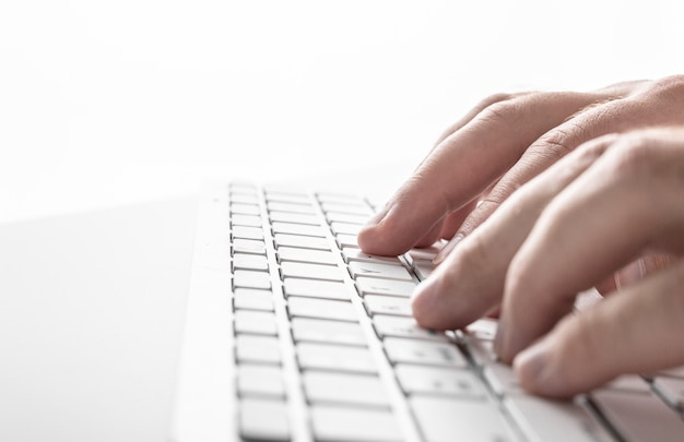 Male hands on a white keyboard on a white