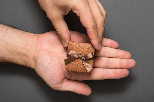 茶色の宝石箱を持つ男性の手。プレゼント。黒の背景