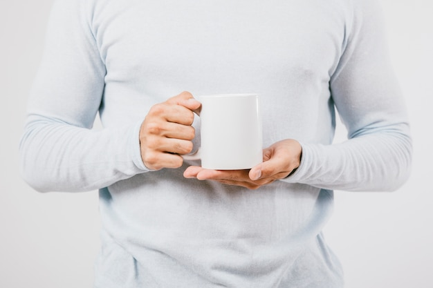 男性の手、コーヒーマグ