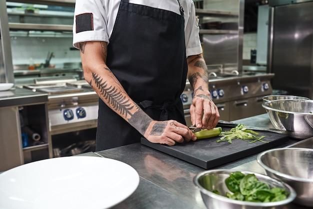 레스토랑 주방에 서 있는 동안 샐러드를 위해 오이 껍질을 벗기는 아름다운 문신이 있는 남성 손