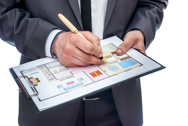 Male hands with clipboard and house plan on it
