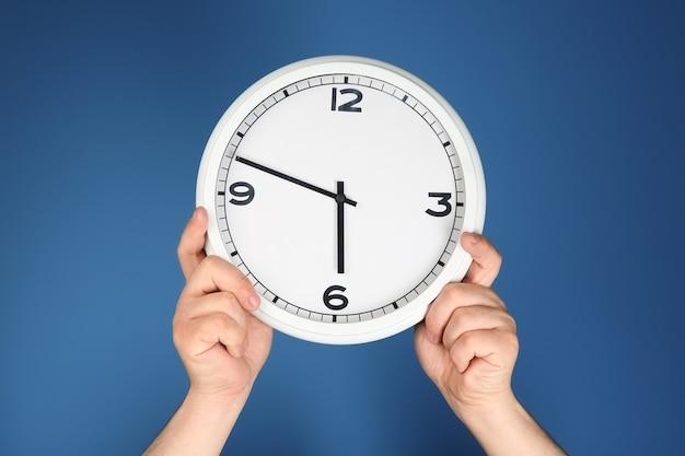 색상 표면에 시계와 남성 손입니다. 시간 관리 개념