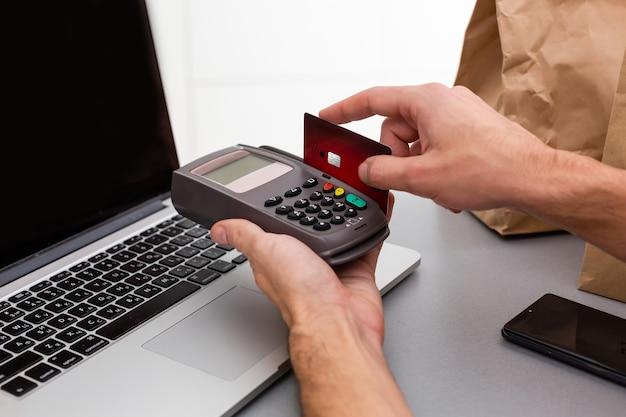 흰색 배경에 고립 된 카드 기계 또는 pos 터미널에 신용 카드를 가진 남성 손