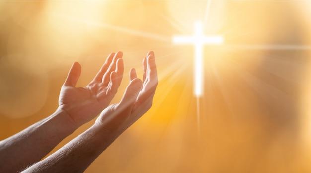 ライトの十字架を持つ男性の手
