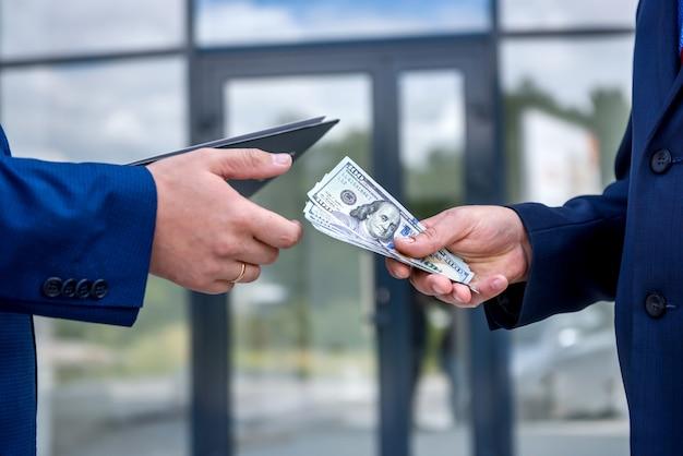 屋外でドル紙幣と男性の手がクローズアップ