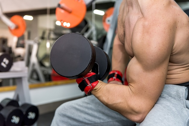 Male hands with dumbbells in gym closeup
