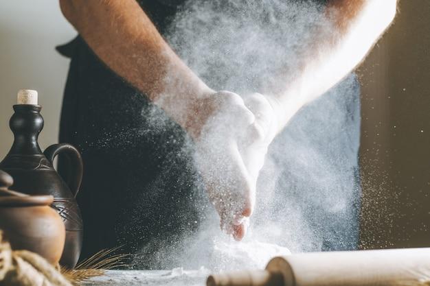흙 냄비와 기름 병, 롤링 핀 옆에 있는 반죽 위에 밀가루를 든 남성의 손. 요리하는 동안 어두운 테이블 위에 밀가루 튀김